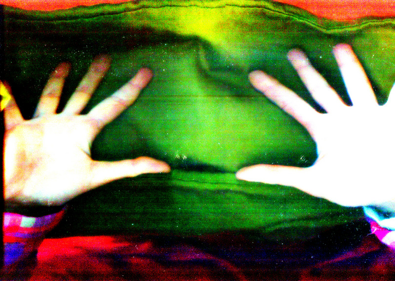 Two hands, blurry with bright green background
